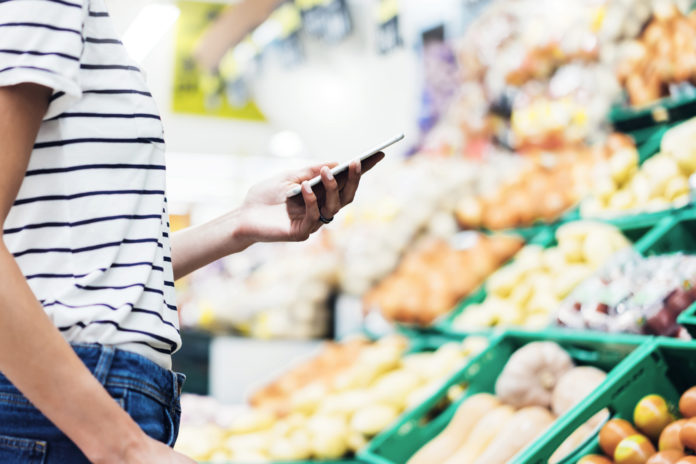 Individual looking at phone in front of produce